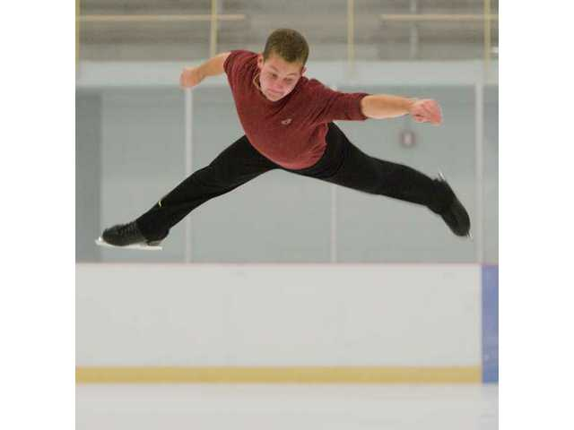 Chad Phillips, a 17-year-old Hart High student, leaps on the ice at Ice Station Valencia on Monday.