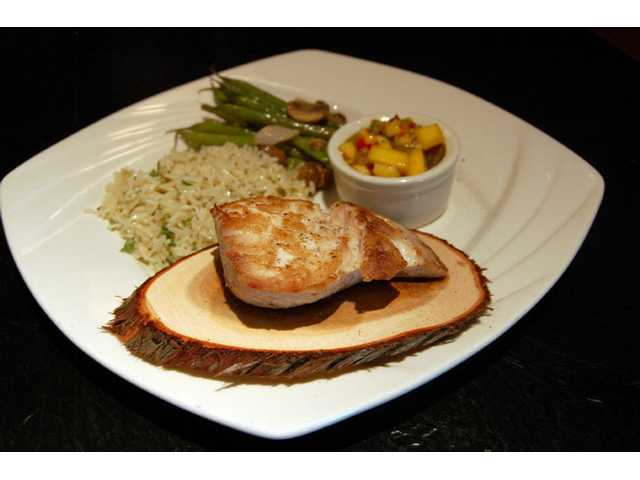Mahi Mahi ($23.95) oven roasted on a cedar plank served with steamed rice and Kentucky pole beans with shallots and mushrooms. Salt Creek Grille has added several new menu items for spring and lowered prices on 90 percent of the restaurant's menu.