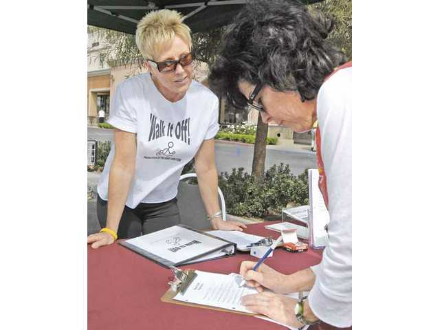 Chris Morley, owner of Walk It Off, left, signs up Linda Abrams of Valencia.
