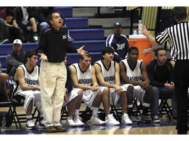 Former Saugus High boys basketball head coach Jeff Hallman, standing far left, gestures to an official in his last home game Feb. 15 against Burroughs. The 49-year-old Hallman resigned after 14 years on Tuesday.