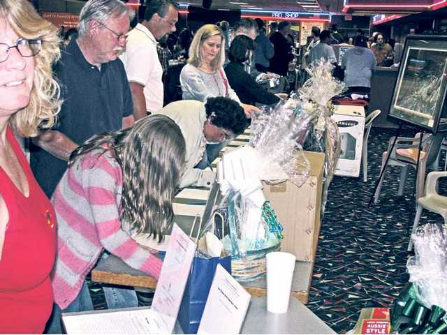 Bidders participate in silent auction.