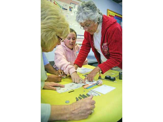 Rancho Pico Junior High School student Taylor Reid, center, helps SCV Zonta Club members Joann Rodroguez, left, and Patt Willet build robots.