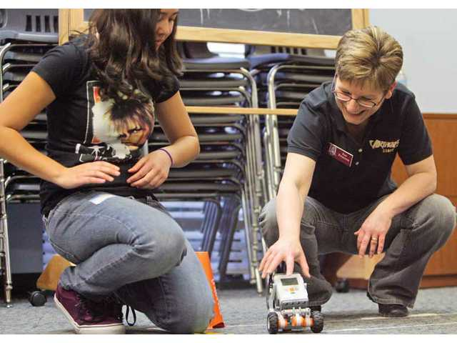 SCV Zonta Club member Sue Peterson, right, and Hart High student Kani Ebner, left, test out their robot after it was built and programmed.