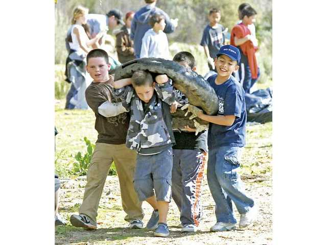 A group of Rio Vista Elementary third-graders carry an old tractor tire from the wash.