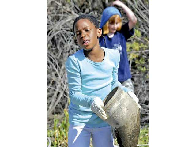 Rio Vista Elementary third-grader Ehimomen Edo carries an old piece from the wash behind her school as she participates in a Clean-Up Day Friday.