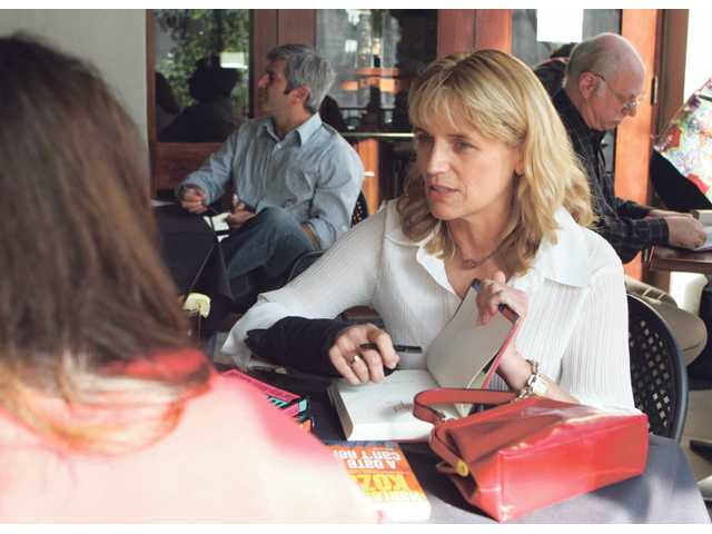 Author Harley Jane Kozak, second from right, signs one of her books Saturday during AfterWORDS, a fundraiser hosted by the Santa Clarita Valley Scholarship Foundation at Salt Creek Grille. Four authors discussed, sold and signed their books. The ticketed event raised money for scholarships to help graduating seniors of the William S. Hart Union High School District continue on to higher education.