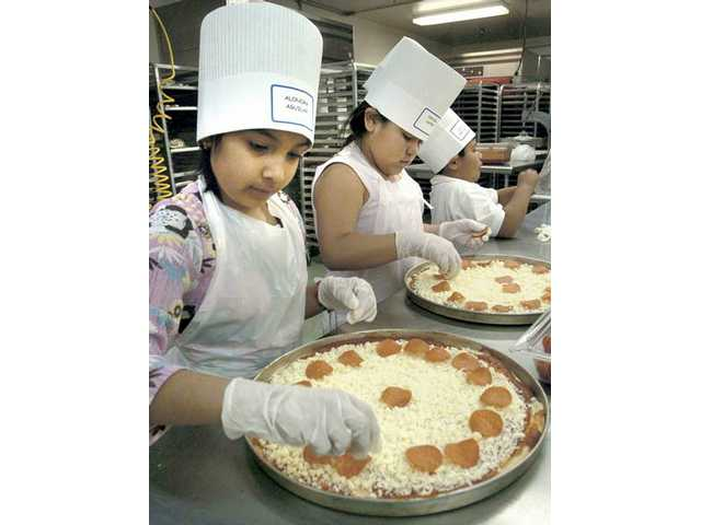 Newhall Elementary fourth-graders Alondra Aguilar, left, and Cynthia Castro make pizzas at the food agency.