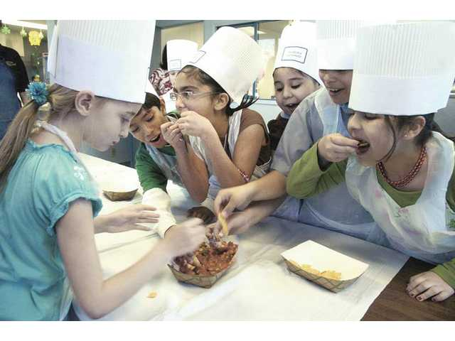 Newhall Elementary fourth-graders taste the salsa they made at the SCV School Food Services Agency on Thursday.