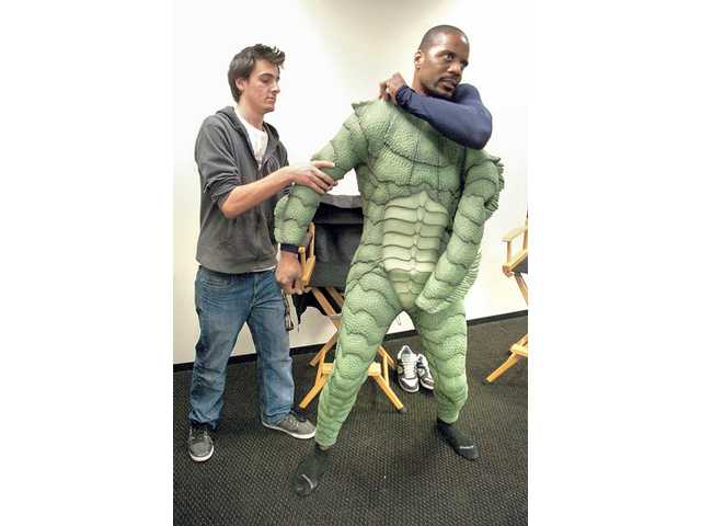 "Production assistant Travis Berger, left, helps actor Carey Jones put on his ""creature"" suit as he prepares to film a scene for ""United Monsters Talent Agency"" at the Borax building on Tourney Road in Valencia."