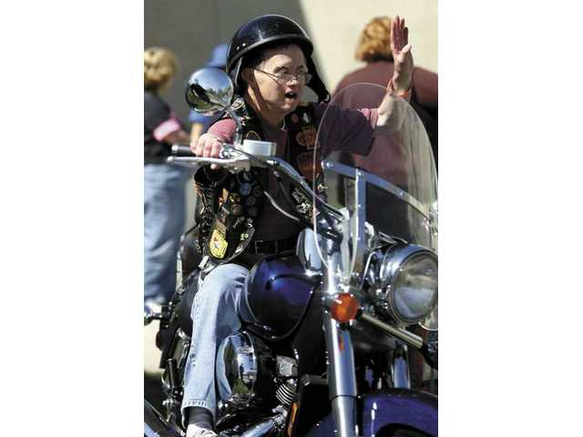 Los Angeles Retarded Citizens' Foundation Ranch resident Charles Kegley waves to his friends as he sits atop a motorcycle Saturday afternoon at the first annual Bikers for Christ benefit ride. The ride helped raise money for the LARC Ranch.