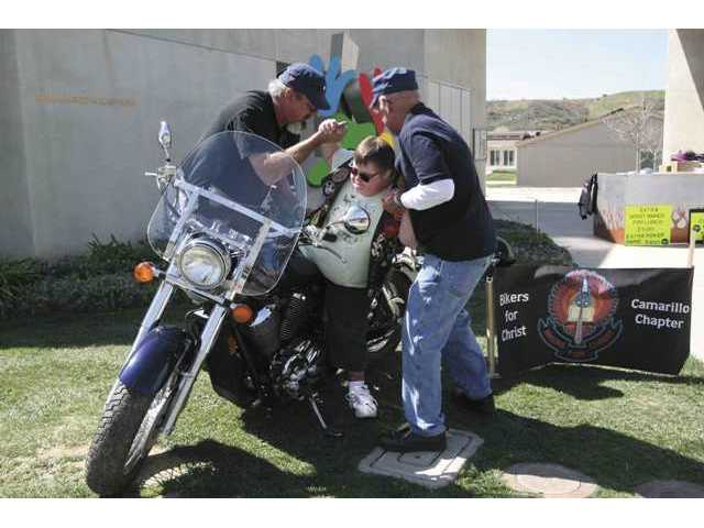 Joe Ramboldt, left, and Michael O'Brien, right, help LARC resident Geanne Westin safely get on a motorcycle so she can have her picture taken.