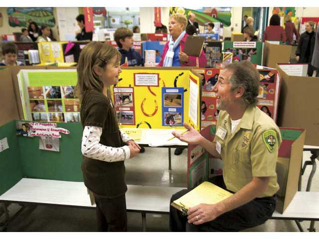 "Ranger Frank Hoffman of the Placerita Nature Center converses with fourth-grader Jenna Miladin about her science project titled ""How much exercise is needed to bring a horse's heart rate up (To a level that provides a sufficient amount of exercise)"" at Newhall Elementary School Monday morning."