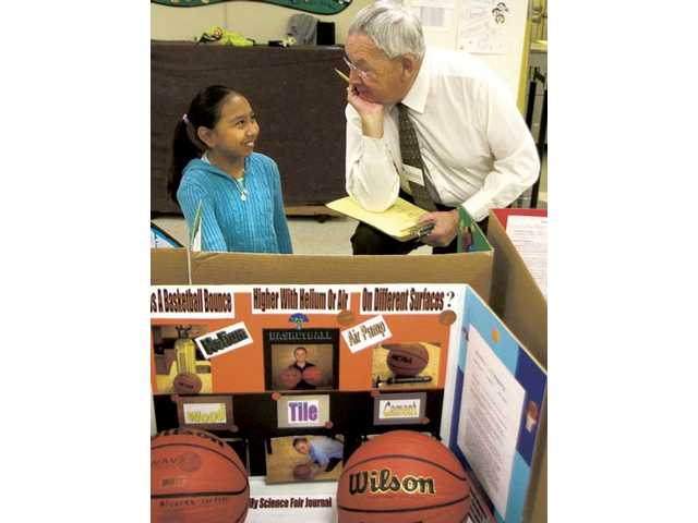 "Estefani Jimenez, fifth-grader at Newhall Elementary School, shares her information collected for her science project titled ""Which water freezes faster, tap water or salt water?"" with judge Dr. Mike McGrath Monday morning."