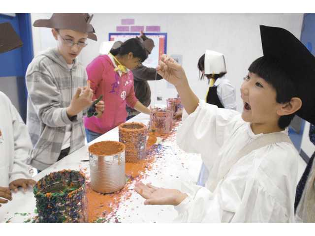Fifth-grader Reid Bowman, right, reacts as he makes a wax candle as they did in Colonial times at the Colonial Day event at Wiley Canyon Elementary School Friday.