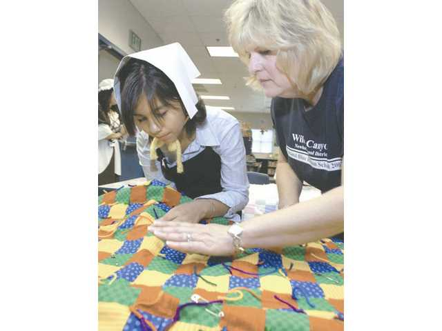 Fifth-grader Ana Olivor, left, gets a hand from quiltmaker Mona Ravenstine as she works on an old fashioned quilt at the Colonial Day event at Wiley Canyon Elementary School on Friday. Students learned about how everyday people lived more than 300 years ago for the occasion.