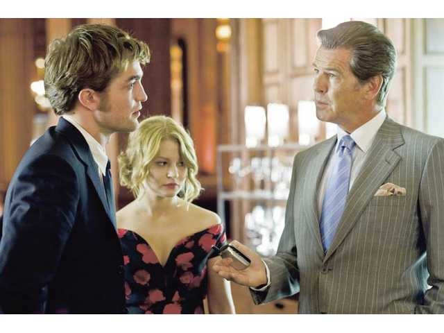 "Robert Pattinson, left, Emilie de Ravin, center, and Pierce Brosnan are shown in a scene from ""Remember Me."""