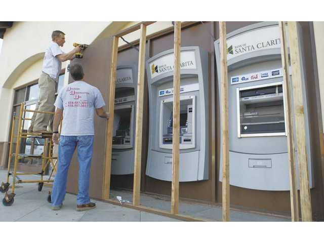 Construction managers, David Evilsizer, left, and Ken Green remove plywood sheets as the Bank of Santa Clarita ATM machines are unveiled in the Plaza at Golden Valley Wednesday.