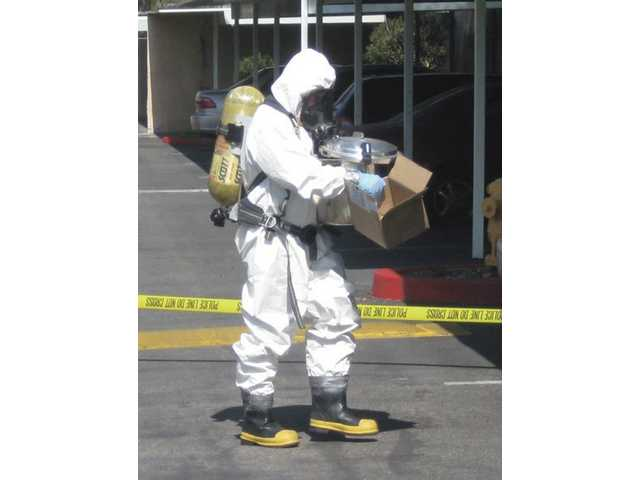 A Los Angeles County Fire Department Hazardous Material Team specialist carries hallucinogenic mushrooms from an apartment in Canyon Country. Santa Clarita Valley sheriff's deputies busted a large mushroom farm operating from the apartment.