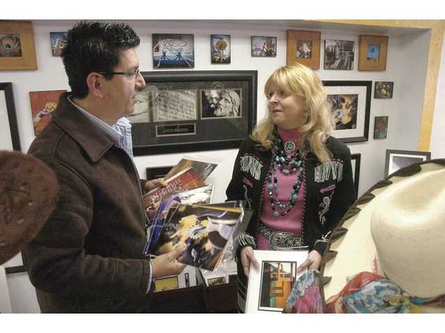 Photographer Frank Lozano and OutWest store co-owner Bobbi Jean Bell discuss photos for display in the store in Newhall. Lozano's fine art photography will be on display in the store through the end of the month.