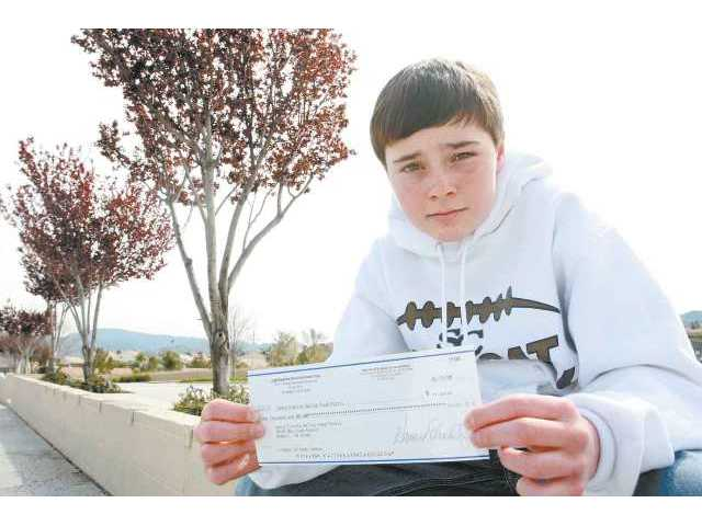 La Mesa Junior High student Dane Cannon displays the check for $1,000 he received from TV executive producer Howard Schultz, who read about Cannon's Food Pantry drive in The Signal and stepped up.