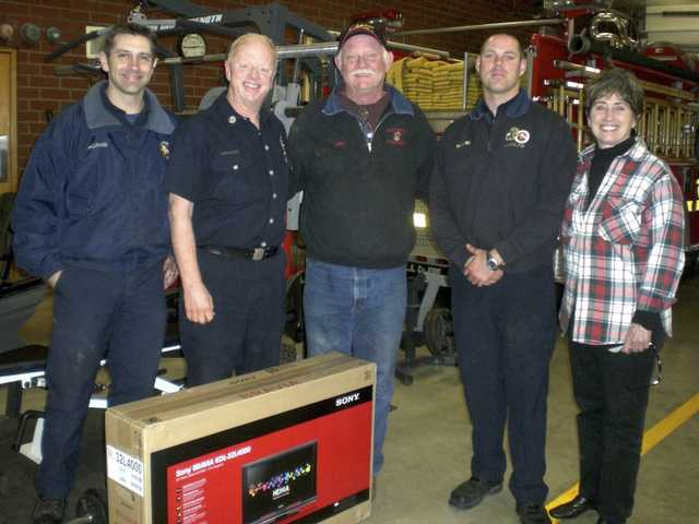 Ruthann Levison, right, and John Higby, center, present firefighters a HDTV purchased by members of the Sand Canyon Homeowners Association.
