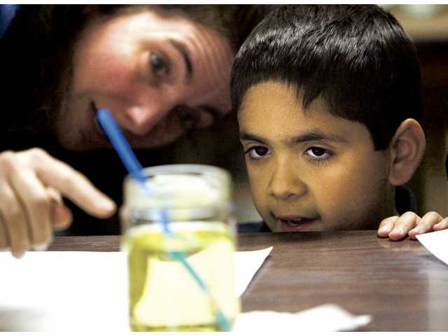 Seven-year-old Brandon Arana and teacher Lisa Melcombe-Weiseman take a closer look on a science experiment which explains light and lenses, Monday afternoon at the Church of Nazarene's home-school classes.