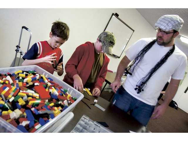 Teacher Vincent Plummer makes sure students Kampton Nuttall, 11, left, and Joseph Berlinger, 10, are building their tanks properly in the LEGO engineering class at the Huckleberry Creative Learning Center.