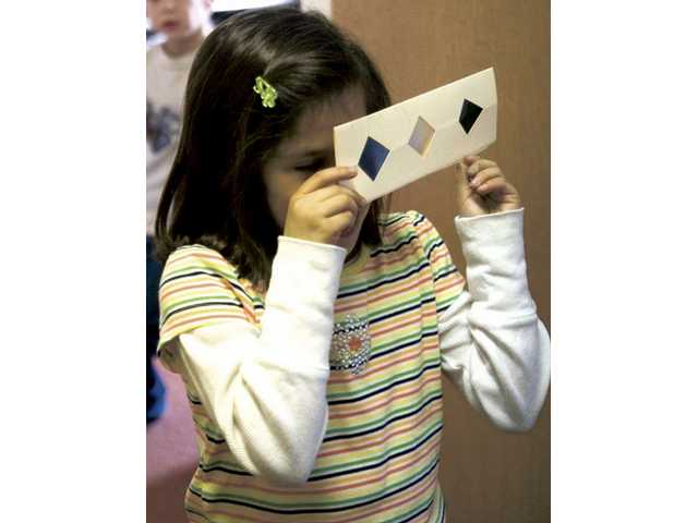 Six-year-old Christina Madugno tries to unveil a secret code after working on a project in a art and science of light and color class at the Huckleberry Creative Learning Center Monday afternoon.