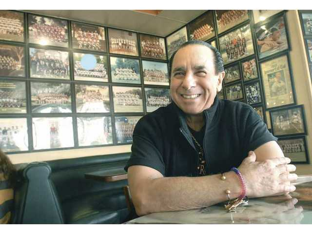 Joe Comella, owner of Final Score in Newhall, sits at a table in his restaurant. The walls of the restaurant are lined with hundreds of photos of SCV sports teams and celebrities.