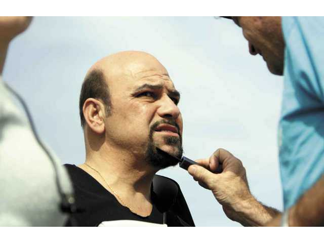 "A makeup artist applies his craft on actor Jon Polito, who plays Captain Sludge in the upcoming indie film ""Super Capers"", during the movie's production on Wednesday. The week-long production shut down the Golden Valley bridge in Canyon Country."