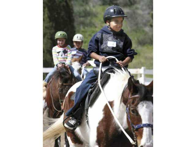 Eight-year-old Junior Villafana rides Apache during the Sheriff's Posse community outreach program Saturday.