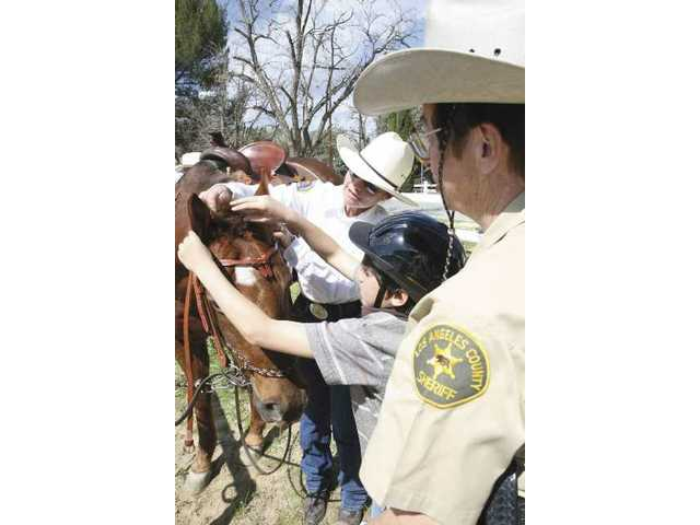 Santa Clarita civilian volunteer Glenda Warnock (left) and San Dimas Posse Sheriff's Reserve officer Susan Flores (right) help Raymond Ibrahim, 8, bridle the horse the boy got to ride Saturday morning.