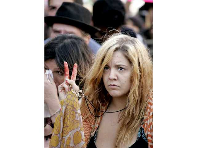 A young woman flashes the peace sign following a moment of silence during a rally Saturday commemorating the fifth anniversary of the Iraq War.