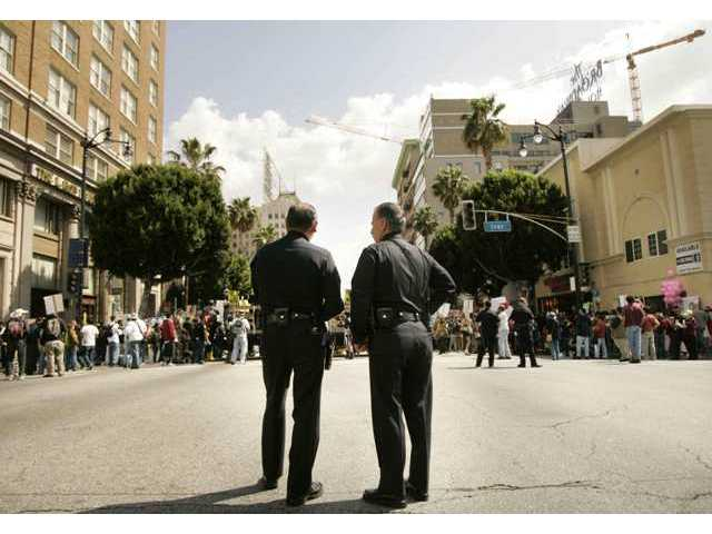 Two Los Angeles Police Department officers stand watch prior to the start of Saturday's ANSWER Coalition march through Hollywood. There were no arrests during the several-hour event.