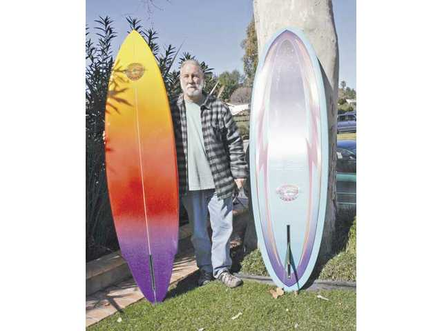 Ray Moss stands between two of his custom-built surfboards.