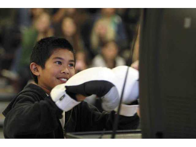 Sierra Vista Junior High seventh grader Jedd Bautista tests out a boxing video game during the preview session of the school's annual fitness fundraising drive.