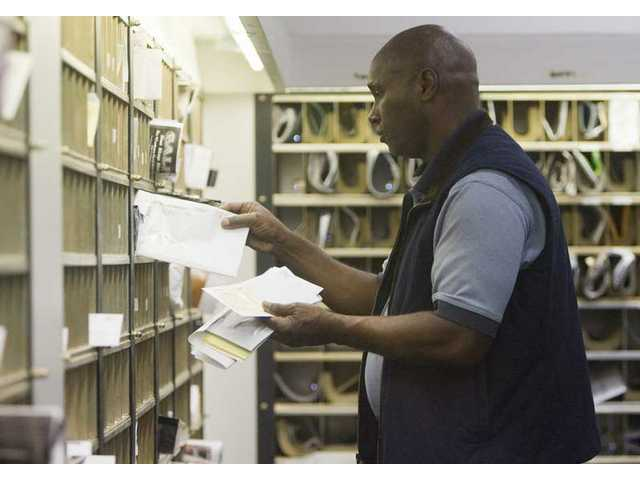 Sam Donn, clerk at the new Castaic Post Office, organizes mail in the correct P.O. boxes Monday morning.