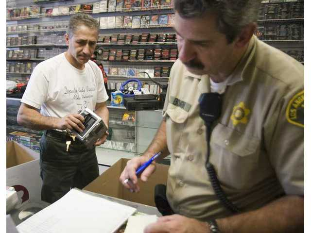 Sheriff's Deputy Alex Vaziri, left, and John Bomben make a list of serial numbers of game consoles at at Game World in Canyon Country. Co-owners Rodney Witfield and Gary Owen were arrested Wednesday morning for not having proper licensing for second-hand items.