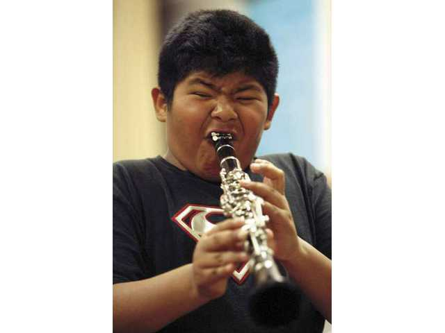 Jose Baltazar, a McGrath Elementary third-grader, tests a clarinet during the school's instrument petting zoo on Tuesday. Students were allowed to try out a variety of instruments.