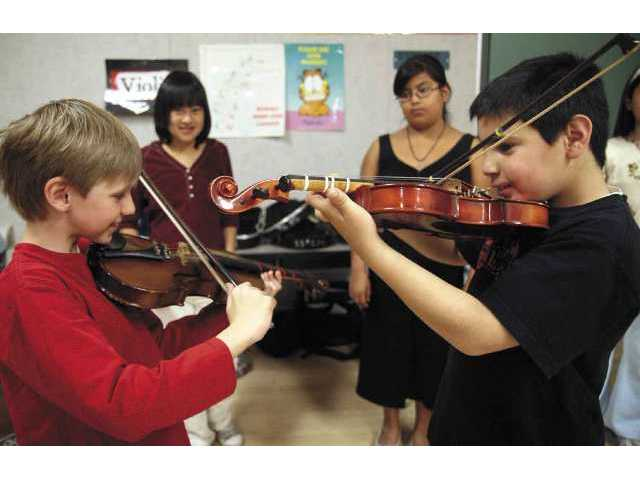 Third-graders Geoffrey Eriksen, left, and Eli Habr, right, play violins as fifth-grade music students Michelle Gatchalian, back left, and Nancy Espejel watch the duo at McGrath Elementary on Tuesday.
