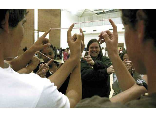 Canyon High School's Samantha Halladay (middle right) Cierra Corbett (middle left) and classmates perform different movements while holding straws during the Breaking Down the Walls diversity program's team-building exercise on Wednesday morning.