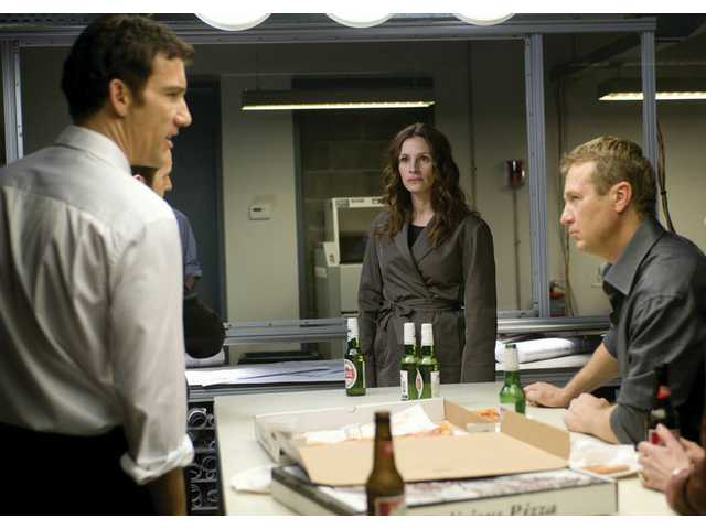 "Clive Owen, left, Julia Roberts and Oleg Stefan are shown in a scene from ""Duplicity."" The spy thriller from Universal is rated PG-13 for language and some sexual content."