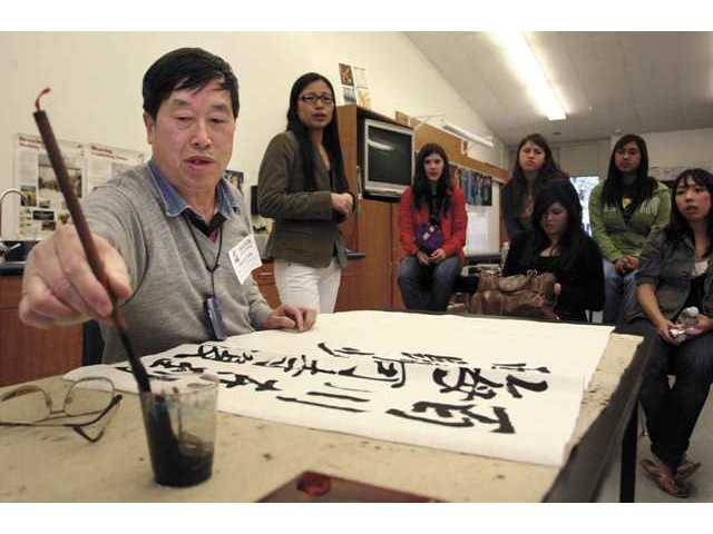 World-famous Chinese calligrapher Dong Yi-Lan demonstrates his art to Saugus High School students during a Tuesday lunchtime presentation.
