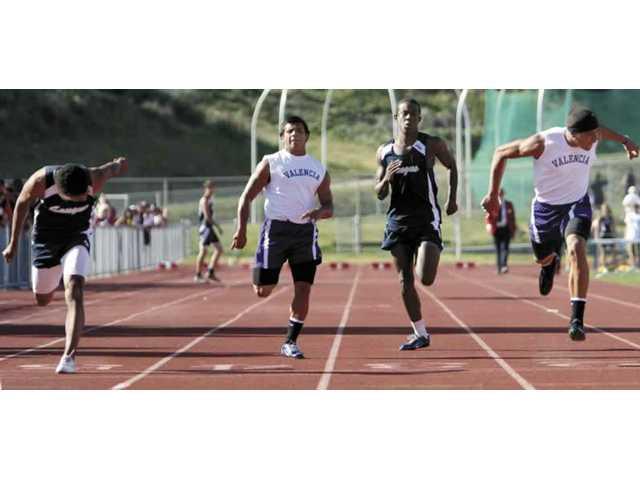 Boys varsity sprinters compete in the 100 meters.