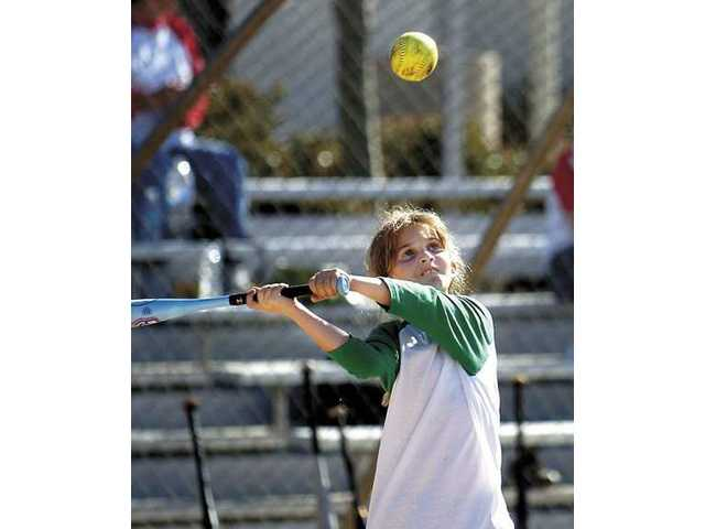 Rosa Scupine, 9, from Los Angeles, swings at the ball and hits it for a single during a family reunion at Central Park.