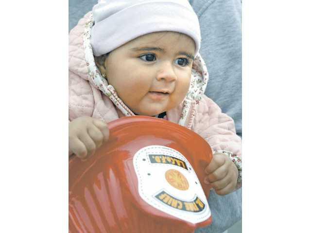Alexandra Acevedo, 7 months, of Valenca, found her junior fire helmet a tasty treat at the Emergency Expo held at College of the Canyons Saturday.