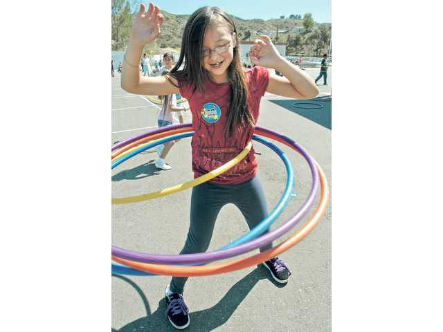Mint Canyon Community School third-grader Sabrina Shehane exercises with four hula hoops, as she participates in the Jump Rope for Heart event the school hosted on Thursday. More than 100 other students in grades one through six took part in the action.