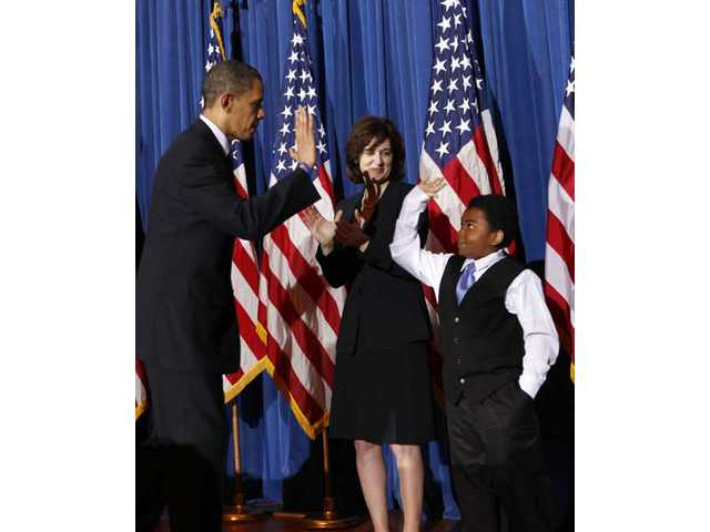 President Barack Obama high-fives Marcelas Owens of Seattle, after speaking about the health care reform bill, Tuesday, March 23, 2010, at the Interior Department in Washington. Behind them is Vicki Kennedy, widow of Sen. Ted Kennedy.