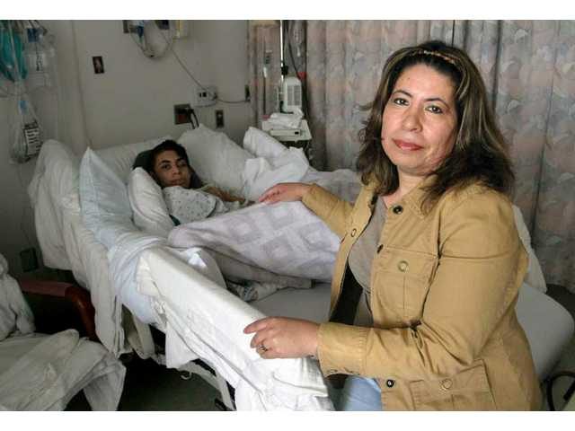 Zoila Guerra, of Saugus, sits in the room of her youngest son 16-year-old Kevin Gomez at Henry Mayo Newhall Memorial Hospital on Monday afternoon. Both of Guerra's teen sons were injured after a car accident