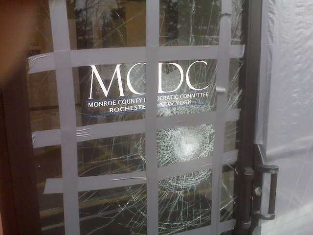 "This picture provided on Wednesday, March 24, 2010 by the Monroe County Democratic Committee in Rochester, N.Y. shows damage to their office after a glass door was struck with a brick with a note reading ""Exremism in Defense of Liberty Is no Vice"" sometime between late Saturday, March 20, 2010 and Sunday, March 21, 2010."